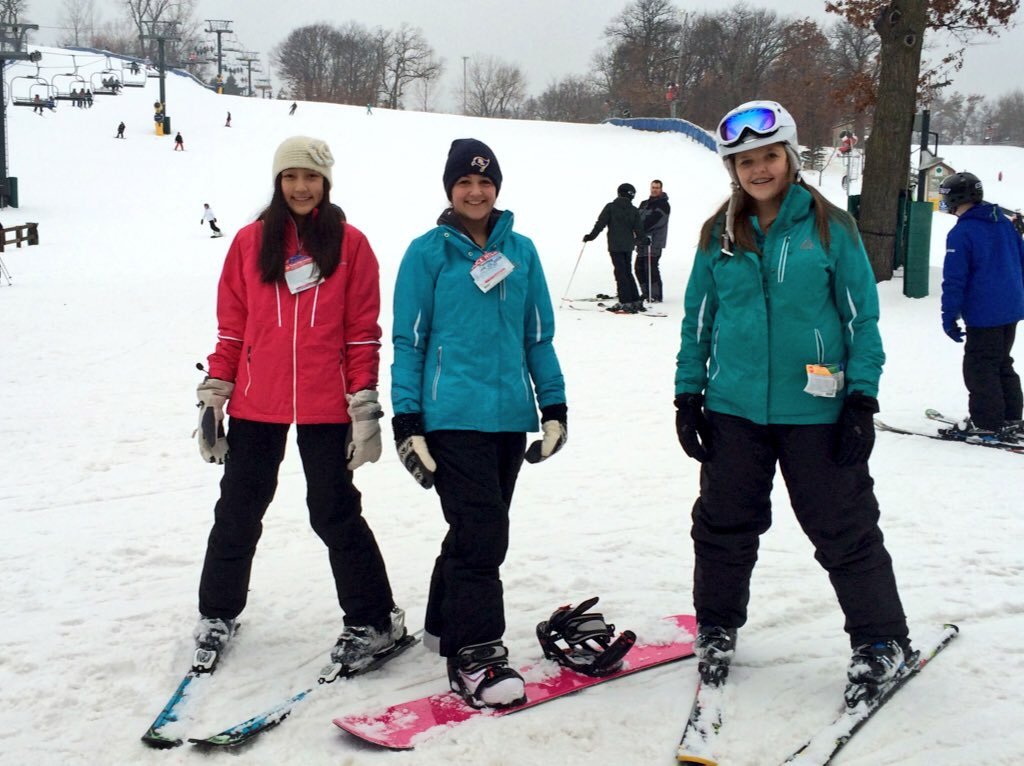 Three girls in winter clothing-- two on skis and one on a snowboard at a ski hill.