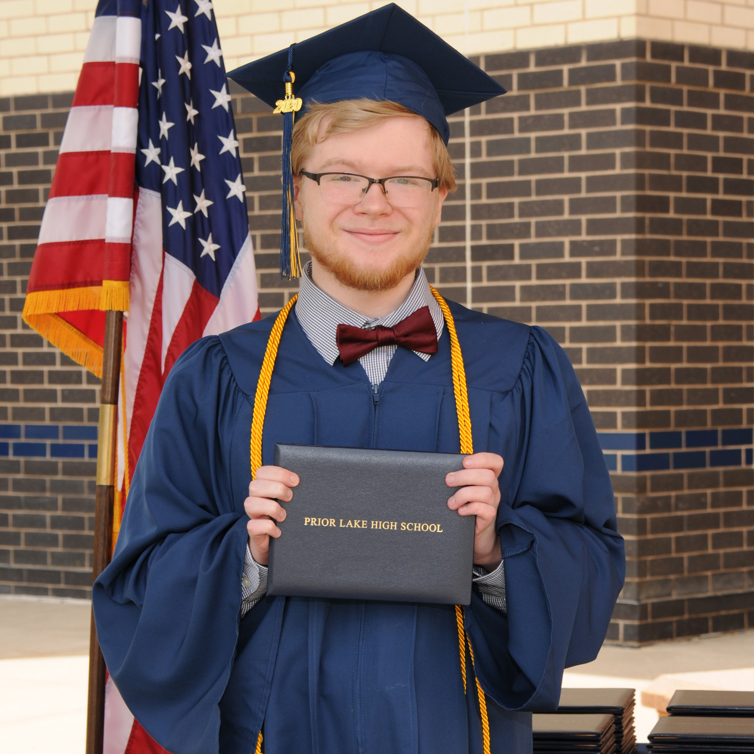 Student in a bow tie, cap and gown, holding up a PLHS diploma folder