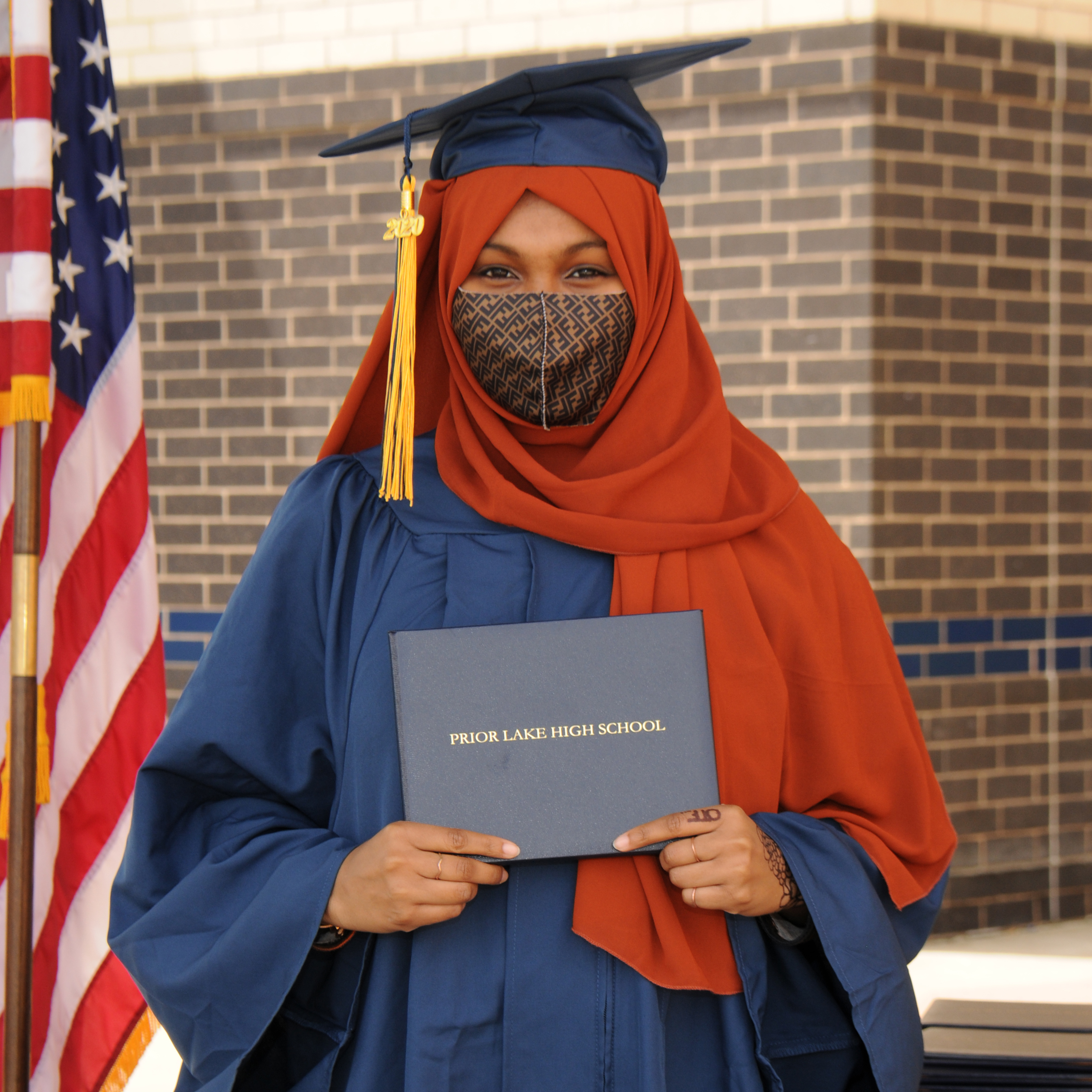 Student in a hijab, graduation cap and gown and a face mask, holding a PLHS diploma folder